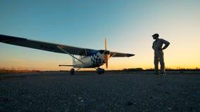 Flieger, der eine Fläche betrachtet Männlicher Pilot steht auf einer Rollbahn und betrachtet ein Flugzeug auf einem Sonnenunterga stock video footage
