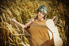Flier child. Little dreamer girl playing with a cardboard airplane in the wheat field. Childhood. Fantasy, imagination Royalty Free Stock Photos