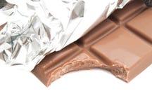 Fliesen der Milchschokolade in einer Folie auf Weiß Lizenzfreie Stockbilder