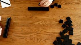 Fliesen werden auf Gestelle zu Beginn eines Gesellschaftsspiels gesetzt, das auf gespielt wird, ooden Tabelle stock footage