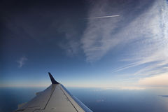 Flight. Airplane wing against sky and sea stock photography