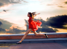 Flight. Running on the roof of a young woman Stock Photos