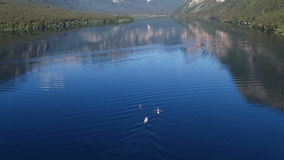 Flight above amazing Bohinj Lake in the morning. People are training in rowing. Blue deep water and Julian Alps mountains. stock video footage