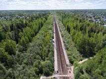 Flight above country railroad and rural platform station between villages, summer season Stock Photos