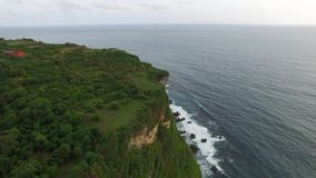 Flying along high cliffs of rocky ocean shore. Flight above high cliffs of the rocky shore of Indian Ocean with green vegetation on top. The coastline of Uluwatu stock footage
