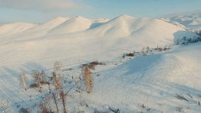 Flight across a winter road to the mountains. Aerial shot stock footage