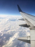 In flight. Air plane wing in flight with a blue sky and fluffy white clouds below Stock Images