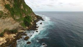 Flying along high cliffs of rocky ocean shore. Flight along the high cliffs of the rocky shore of the Indian Ocean. The frothy waves of the ocean break on sharp stock video