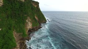 Flying along high cliffs of rocky ocean shore. Flight along the high cliffs of the rocky shore of the Indian Ocean. The frothy waves of the ocean break on sharp stock video footage
