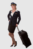 Flight attendant. Full body of a blond caucasian woman wearing flight attendent hat and suit holding on to a suitcase over white royalty free stock image