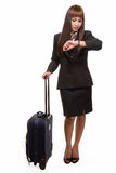 Flight attendant. Full body of Asian woman in black business suit skirt with suitcase looking at wrist watch Royalty Free Stock Image
