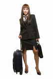 Flight attendant. Full body of Asian woman in black business suit skirt with suitcase standing over white background Stock Photos