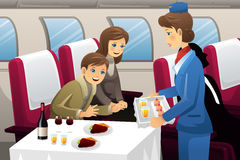 Flight attendant in an airplane. A vector illustration of flight attendant serving a passenger in an airplane Stock Photography