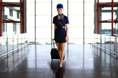 Flight attendant carrying her luggage Stock Image