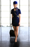 Flight attendant carrying her luggage Royalty Free Stock Images