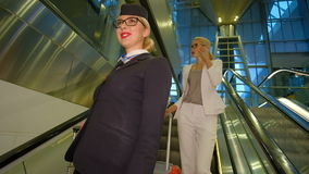 Flight attendant with glasses goes down the escalator and smiling. Flight attendant with glasses comes down the escalators and smiling. Woman holds suitcase stock video footage
