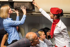 Flight attendant help passenger with luggage cabin Royalty Free Stock Image