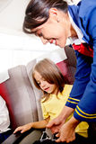 Flight attendant helping a kid Royalty Free Stock Images