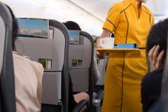 Flight attendant offering beverage to a passenger. In flight jurney Stock Image