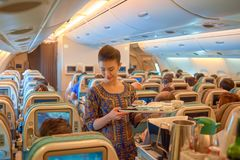 Flight attendant serve food and drinks. SINGAPORE - NOVEMBER 03, 2015: flight attendant serve food and drinks to passengers on board of Singapore Airlines Airbus Royalty Free Stock Photography
