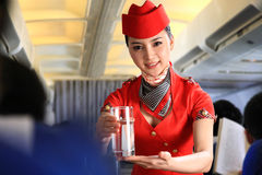 Flight attendant serving people on airplane Stock Image