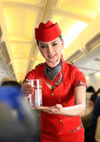 Flight attendant serving people on airplane Royalty Free Stock Photo