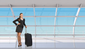 Flight attendant standing with luggage in airport Royalty Free Stock Photo