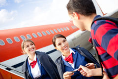 Flight attendants welcoming passenger Royalty Free Stock Photo
