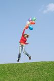 Flight by balloons. Beautiful young girl with a sheaf of the balloons, jumping on a green grass on a background of the blue sky Stock Photography
