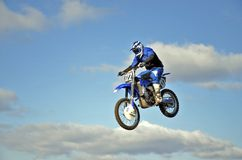 Flight of biker MX against the blue sky and clouds Royalty Free Stock Images