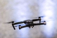 The flight of a black unmanned quadrocopter on a light blurred background. The flight of a black unmanned quadrocopter on a light blurred background Royalty Free Stock Image