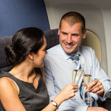 Flight cabin business partners toasting champagne. Airplane travel passengers Stock Photo