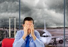 Flight canceled by bad weather. Businessman crying by delayed flight because the stormy weather at the lobby airport Stock Photography