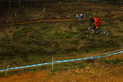 Flight Control Downhill Fox Racer MTB. Downhill MTB Cycle Racer Fox Red apparel gear flying mid air over the last big jump at the World Cup Downhill Mountain Royalty Free Stock Photography
