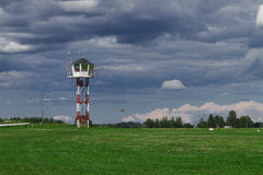 Flight control tower on a small grass airfield with glider landing in the background in a bad weather Stock Image