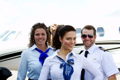 Flight crew in front of plane Stock Photo