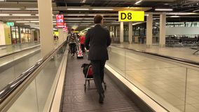 Flight crew member and passengers use horizontal airport escalator