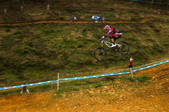 Flight Downhill Racer MTB. Downhill MTB Cycle Racer Greg Minnaar Santa Cruz syndicate gear flying mid air over the last big jump at the World Cup Downhill Royalty Free Stock Image