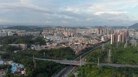 Flight of a drone over a hilly city. The frame contains a large number of electric transmission lines. Roads and viaduct, in the background the city of stock video