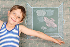 Flight. Of fantasy, schoolboy before chalkboard with drawing of airplane back of open window Royalty Free Stock Photography
