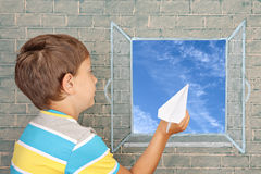 Flight of fantasy. Schoolboy before chalkboard with paper airplane Stock Photo