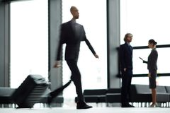 Flight haste. Blurry human figure moving along airport lounge with suitcase and hurrying for flight royalty free stock images