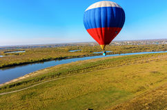 Flight of hot air balloon over river landscape Stock Photo