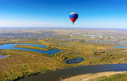Flight of hot air balloon over river landscape Royalty Free Stock Images