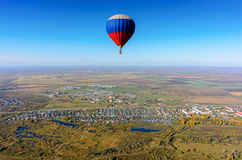 Flight of hot air balloon over rural landscape Royalty Free Stock Photography