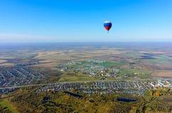 Flight of hot air balloon over rural landscape Stock Photo