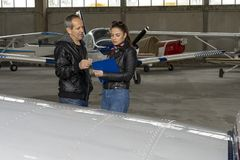 Student Pilot and Flight Instructor Check an Aircraft for Safety in a Hangar. Flight instructor talking to female trainee pilot. They are standing next to small royalty free stock images