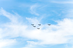 Flight of military fighter planes in white clouds Stock Image