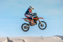 Flight of motorcycle racer on blue sky background Stock Images