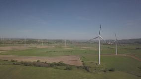Flight near a wind power station in the daytime in the spring. Rotating blades of energy generators. Ecologically clean electricit. Y. Modern technologies for stock video footage
